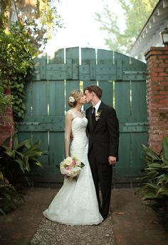 great wedding couple portrait: but what I really like is the faded blue gate, brick pillars,  and pavers on the driveway!  :-)