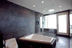 Resort style bathroom with dark accent wall and huge bathtub.