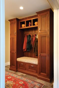 Custom mudroom cabinetry, handcrafted from Sapele with a Honey stain.  A built in bench, drawers below, coat hooks and open shelving above.
