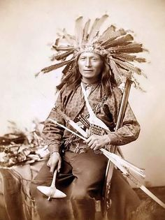 """Here for your perusal is a collectible photograph of """"Little,"""" the instigator of Indian Revolt at Pine Ridge, 1890. It was created in 1891 by Grabill, John C. H., photographer.    The photograph illustrates Little, Oglala band leader, three-quarter length studio portrait, seated, wearing a turkey feather headdress and holding various weapons. He has a Rifle,a Tomahawk, and a Bow and Arrows"""