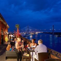 High tops and cozy couches line the exterior of the Bohemian Hotel Savannah Riverfront's rooftop bar, located right on the Savannah the river in the historic district. The river view begets a romantic scene: passing boats and the Talmadge Memorial Bridge.