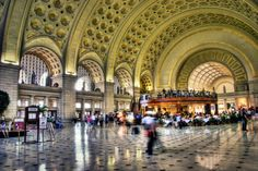 Union Station, Washington, D.C.: The 96-foot high coffered Main Hall ceiling shines with gold leaf, reflecting light onto the expanse of its...