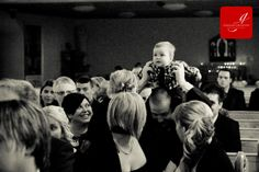 baby being lifted onto the shoulders of his father in the audience during a wedding ceremony www.grahamcrichton.com