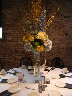 flowers by tina barrera  yellow, blue and white tall centerpieces