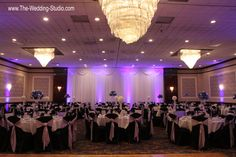 The Grand Ballroom ready for a wedding reception at The Mirage Banquets in Schiller Park. Purple up-lighting glows in the background. Photographed by The Wedding Studio, Schaumburg IL