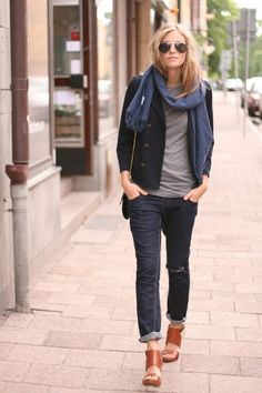 Dark rinse boyfriend jeans and a simple gray tee are given a touch of class and character with when paired with chunky cognac sandals, a shrunken blazer, and accessories like a nearly sheer navy scarf and unassuming chain-link purse.