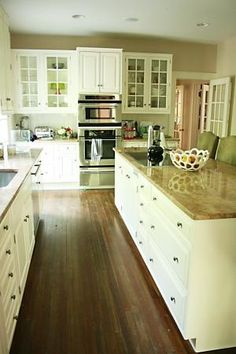 Dark stained wood floors and butcher block countertops warm up the white ceiling, cabinets, and walls.