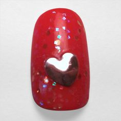 Say it loud with this love-themed custom nail design. Perfect for Valentine's Day!  The red base is topped with chunky glitter. The oversized metal heart is just the right fit.