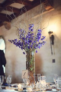 curly willow accented with dark blue delphinium; maybe so a bit less delphinium so the willow is more the focus with just a splash of color to accent it. Cylinder Vase Centerpieces, Tall Cylinder Vases, Blue Centerpieces, Wedding Reception Centerpieces, Wedding Decorations, Table Decorations, Curly Willow Centerpieces, Tall Floral Arrangements, Blue Delphinium