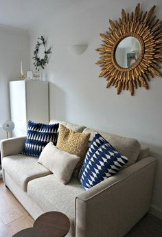 Not on the high street : Christmas Decorations. Metallics, a gold sunburst mirror and a natural wreath with gold and brass accessories. A neutral sofa with dark inky navy velvet and gold cushions.