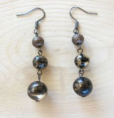 Made using gunmetal wire and hooks, these earrings feature an interestingly textured, milk-chocolate-colored bead and two black and gold painted beads. Found at www.zibbet.com/BokBokJewelry