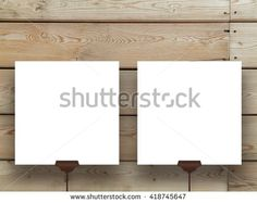 Close-up of two blank square frames supported by clips against brown wooden wall…