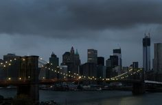 The lights on the Brooklyn Bridge stood in contrast to the darkened lower Manhattan skyline, which lost its electrical supply (storm moving northwest, #Sandy aftermath, early morning, October 30th 2012).