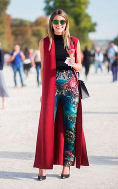 Street style look Helena Bordon usando colete longo vermelho, blusa gola preta, calça colorida estampada. e scarpin preto.