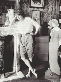 At home, Mistinguett posing next to a reproduction of her image from a poster by Losques (1930s?).