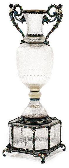 Vase en cristal de roche richement gravé de rinceaux feuillagés et de fleurs, une couronne de godrons à la base de la panse et reposant sur un piédouche.  La monture en vermeil et émail polychrome avec des anses sortant de la tête d'animaux