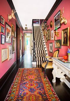 PERFECT ENTRY. Boho Rug, Pink Walls, B&W stripped stairway runner, faux taxidermy in eclectic gallery wall, vintage chair and table. (Sorry Sweetheart...you knew there would be pink.)