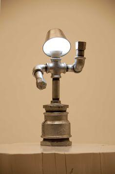 Una lámpara trabajada artesanalmente con tuberías de hierro destinadas en origen a trabajos de fontanería. Representa a una mujer mecanizada.  Puedes personalizar tu lámpara según el estado de ánimo de cada día pintando con un rotulador su cara.  Alimentada a 230 voltios, 25 vatios, se entrega con bombilla de bajo consumo.