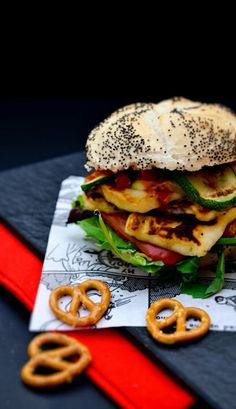A stacked halloumi and red pepper burger layered in a bun with courgette, salad…