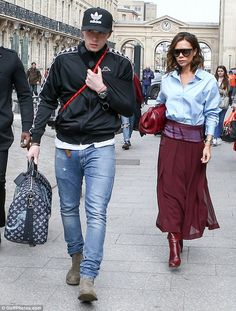 Here they come: Victoria Beckham was joined by oldest son Brooklyn as she arrived in Paris on March 10, 2017