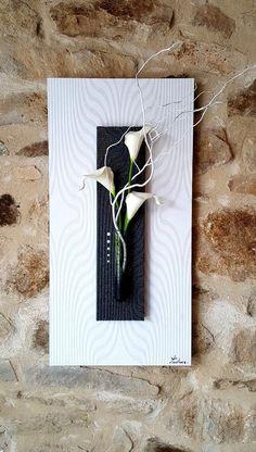 Tableau floral blanc et noir, de taille 60x30 cm, avec motifs en reliefs sur les deux couleurs. Les fleurs sont des arums blancs artificiels, placés dans un soliflore en verre tacheté de noir. Des branches naturelles, peintes en blanc et vernies par mes soins, accompagnent les fleurs et donnent