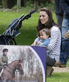 Princess Charlotte smiles in her mother's arms as they watch the equestrians make their way around the course