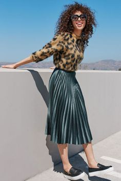 MONDAY: THE PLEATED MIDI-SKIRT Start the week off right: A classic ladylike silhouette—the full accordion skirt—feels modern in a rich metallic hue. Skip the expected silky blouse and rock it with a bold printed sweater and loafer-like slip-on sneaks instead. (Glam statement sunglasses optional.)Toga Leopard Jacquard Knit Wool Blend Sweater, $425, nordstrom.com; Zara Pleated Midi Skirt, $69.90, zara.com; Calvin Klein Women's Jaiden Platform Sneakers, $119, macys.com; Gucci Sunglasses, $330…