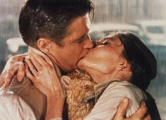 Breakfast at Tiffany's: Paul (George Peppard) brings Holly Golightly (Audrey Hepburn) into a kissing embrace as the rain comes down.