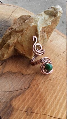 Simple copper wire wrapped ring with Jade beads Very simple ring made of recycled copper wire and one natural green Jade beads Wire is hammered, patinated and polished by hand. The copper has been aged and polished to give a rich patina and depth of color.It is covered with clear