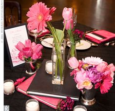 Small vases of gerbera daisies, tulips, and peonies decorated tables. They sat on and around a stack of books wrapped in the signature colors.