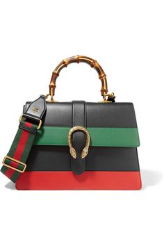Gucci's 'Dionysus' shoulder bag is a celebration of heritage and traditional Italian craftsmanship. Adorned with a burnished gold tiger clasp, this smooth leather piece is paneled with the brand's signature red and green stripes and has a curved bamboo handle. It has a compartmentalized interior and second canvas strap so you can switch up the styling.
