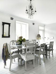 Salle à manger en total look gris pastel su sol au plafond. La table et les chaises dépareillées sont peintes en gris perle. Les touches de vert tendre renforcent l'impression de sérénité