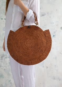 """-Round basket bag with beautiful mesh crochet design -Leather braided handles -Button closure -Organic cotton tie-dye pocket Bag Dimensions: 17 x 4 x 18 in Handle Drop: 5.5 in Model is 5' 8"""" in Raffia is a 100% natural fiber made from Raffia palm leaves. This versatile material is produced from the membrane on the underside of each individual frond leaf. The membrane is taken off to create a long thin fiber, which can be dyed and woven as a textile into products. Traditionally used to make… Round Basket, Basket Bag, Summer Bags, Crochet Designs, Straw Bag, Organic Cotton, Tie Dye, Textiles, Leather"""