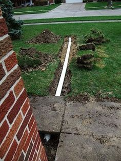 DIY - How to install a drain pipe from the gutter of your house to drain to your backyard.  Pictures of the concrete, burying the pipe, digging the trench, sand backfill and PVC pipe.  Material list and prices.  backfill, cloth, dig, downspout, drain, drainage, gutter, material, pipes, PVC, sand, trench, underground, yard