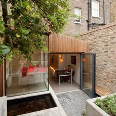 """Residential Architecture: The Jewel Box House by Fraher Architects: """".London-based Fraher Architects have completed a house extension in Islington that is wrapped in larch batons and has a flower-covered roof. Patio Interior, Interior And Exterior, Interior Design, Box House Design, Architecture Résidentielle, Glass Extension, Timber Cladding, Box Houses, London House"""