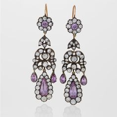 Antique Pink Topaz Diamond Silver Gold Chandelier Earrings. A pair of English Antique 15 karat gold and oxidized silver earrings with diamonds and pink topaz. The earrings have 86 round old European-cut diamonds with an approximate total weight of 7.20 carats, and 8 pear and round-cut pink topaz stones with an approximate total weight of 4.70 carats. In the Georgian-style of girandole earrings. With antique box. Circa 1900-1910.