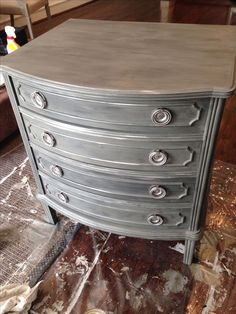From description on web: Annie Sloan French Linen, Graphite dry brush (maybe can do with black wax?), silver on details.
