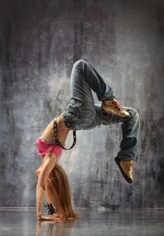 bailarina de danza moderna posa delante de la pared gris de Foto de archivo