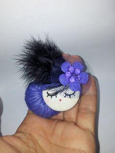 Broche de carita de muñeca, elaborado con tela de algodón, pintura, lana,  etc..