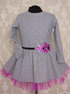 Wizytowa sukienka Pink wykonana z szarej dresówki bawełnianej. Dół kreacji delikatnie rozkloszowany, wykonany z różowego tiulu odszytego podszewką. Przepasana w pasie czarnym paskiem ozdobionym niesamowitym dużym mieniącym się kwiatem. Sukienka posiada długie rękawy oraz kryty zamek z tyłu kreacji.