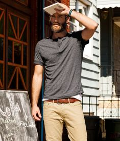 Shop this look for $54: http://lookastic.com/men/looks/charcoal-henley-shirt-and-white-crew-neck-t-shirt-and-brown-belt-and-tan-chinos/401 — Charcoal Henley Shirt — White Crew-neck T-shirt — Brown Leather Belt — Khaki Chinos