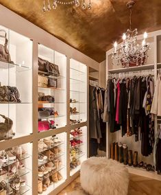 Glam closet features a gold leaf barrel ceiling accented with two crystal chandeliers over built-in lighted display shelves lined with glass shelves filled with designer shoes and bags alongside a round sheepskin ottoman atop wood herringbone floors.
