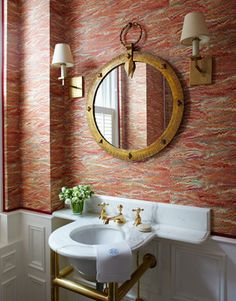Antique French Bathroom - Marbleized paper — Pheasant by Twigs — and a 1940s French metal mirror complement the powder room's vintage marble sink and antique fixtures.