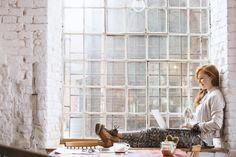 Buy Woman sitting on windowsill with notebook by bialasiewicz on PhotoDune. Beautiful ginger woman sitting on windowsill with notebook