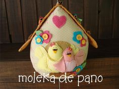 Enfeite para quarto de bebê casa de passarinho.  Pode ser feita também como peso de porta.  Confeccionado em tecidos 100% algodão, apliques de feltro, botões e pau-de-canela. A mamãe recebe colar de pérolas no pescoço.  Tudo bem gordinho e delicado!  As cores podem ser alteradas. A casa pronta mede cerca de 20 cm altura.