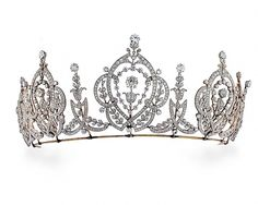 A belle epoque tiara, circa 1905. Designed as five open work oval motifs of intertwining scrolls and foliate sprigs, each cented on a diamond flower, and topped by a similar circular diamond. Each oval is separated by foliate spacers and is supported by a plain band of platinum.