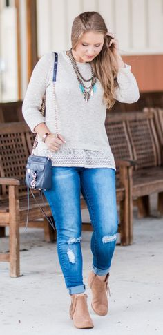 Cream sweater with lace ruffle, destroyed denim jeans, navy crossbody bag, antiqued gold and turquoise statement necklace, and Lucky Brand Beeliner fringe booties styled by blogger Ashley Brooke Nicholas. Click through this pin to see this cute fall outfi
