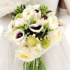 purple-centered white calla lilies, ranunculus and peonies, with green accents of coffee berries and ferns