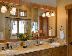 Honey-colored wood frames the master bathroom's mirror and windows, offering a visual connection with the home's Douglas fir logs.