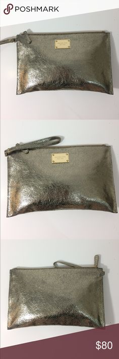 Michael Kors clutch Michael Kors jet set travel large gold clutch with wrist strap. Used in excellent condition. Has a few spots on the inside. Michael Kors Bags Clutches & Wristlets